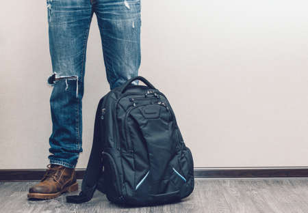 Young fashion mans legs in jeans and boots with backpack on wooden floor photo