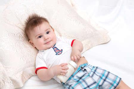 teteros: Poco hermoso bebé satisfecho por el que se sostiene la botella mientras que con los alimentos Foto de archivo