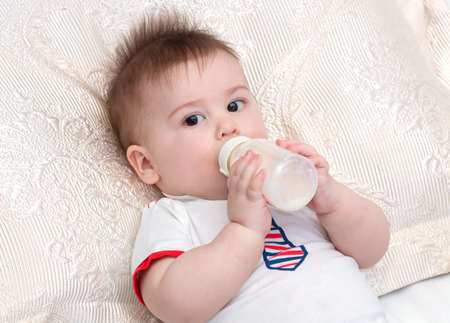 cereals holding hands: Little beautiful baby laying while holding bottle with food and eating