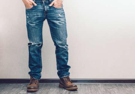 Las piernas del hombre joven de la manera en pantalones vaqueros y botas en el piso de madera Foto de archivo