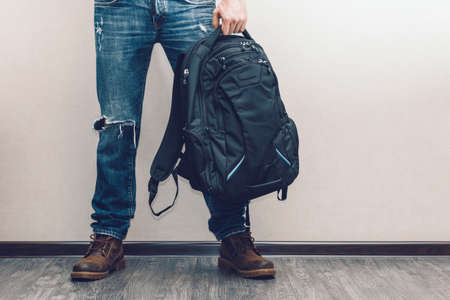 Young fashion mans legs in jeans and boots holding a backpack on wooden floor