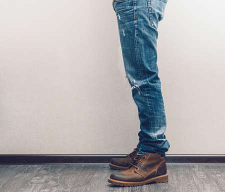 Young fashion mans legs in jeans and boots on wooden floor