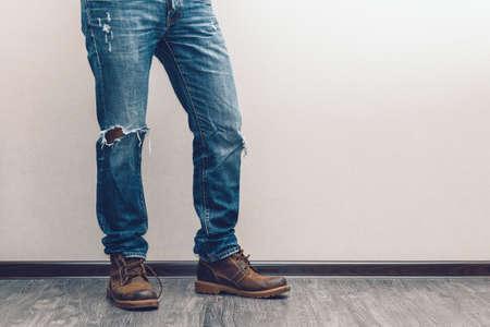 젊은 남자의 다리 청바지와 부츠 나무 바닥에 패션