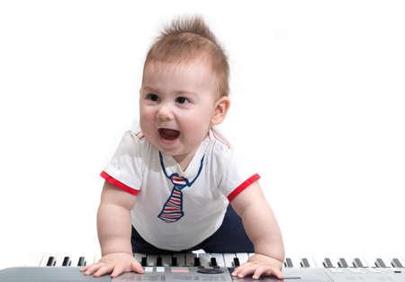 Little baby enjoying playing on piano (synthesizer), isolated on white