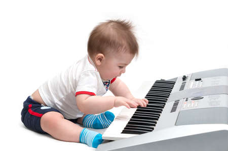 Little baby playing on piano (synthesizer), isolated on white