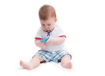 작은 웃는 아기 앉아서 화이트 절연 스마트 폰을 들고 스톡 콘텐츠