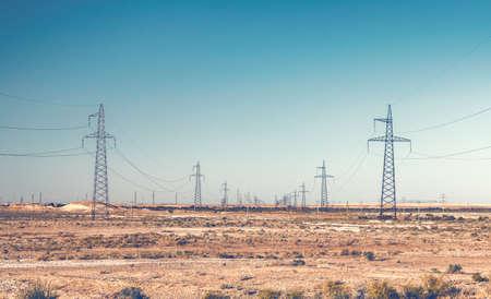 isolator high voltage: Rows of high voltage power line pylons in desert