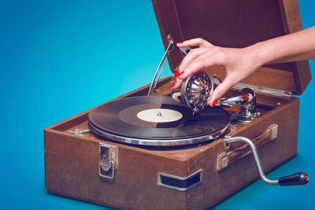 Old gramophone portable à la main féminine pin-up style isolé, sur fond bleu avec un espace vide