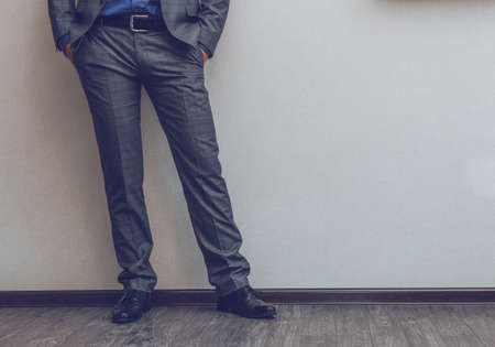 Young fashion businessmans legs in classic suit and shoes on wooden floor Reklamní fotografie
