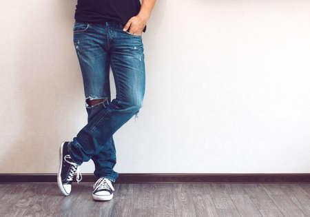 pieds sales: les jambes de mode jeune homme en jeans et baskets sur le plancher en bois Banque d'images