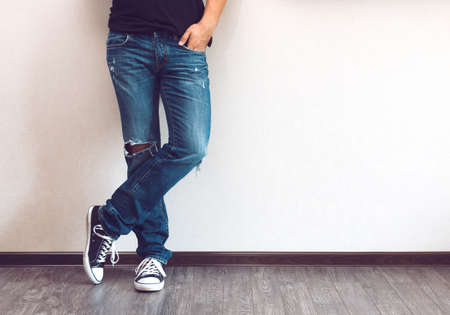 dirty feet: Young fashion mans legs in jeans and sneakers on wooden floor Stock Photo