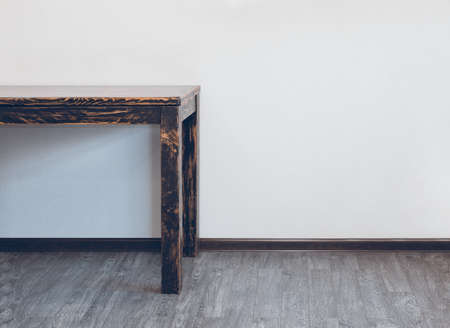 Part of empty wooden table in room over light wall with empty space