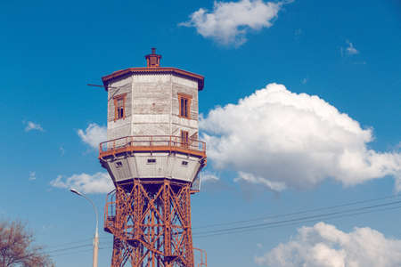 Old wooden water tower with keeper room over blue sky Stock Photo