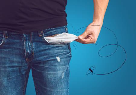 dinero: Pobre hombre en pantalones vaqueros con el bolsillo vacío y el concepto dibujado mosca