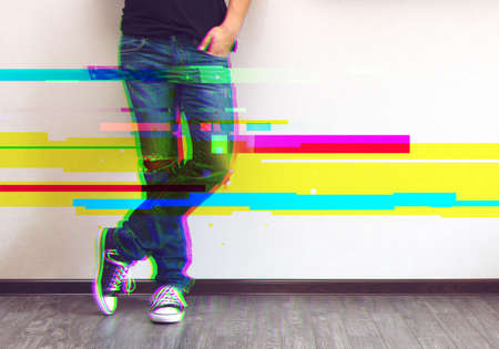 Glitched style photo of young fashion mans legs in jeans and sneakers on wooden floor Stock Photo