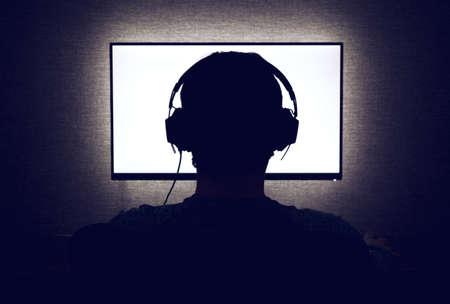 헤드폰에 남자는 어두운 방에 빈 모니터 앞에 앉아