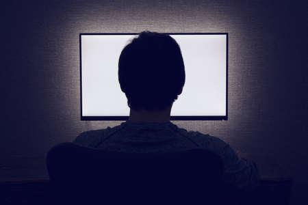 男が暗い部屋で空白のモニターの前に座っています。 写真素材