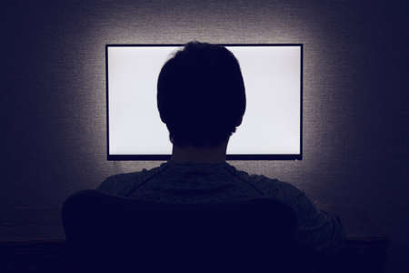 Man sits in front of a blank monitor in dark room Фото со стока