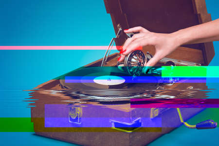 portable failure: Old portable gramophone with female hand pin-up styled isolated, on blue background with empty space and glitch effect Stock Photo
