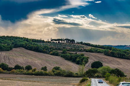 Beautiful picturesque hills with farm house and cypresses in Tuscany, Italy, at summer, toned image