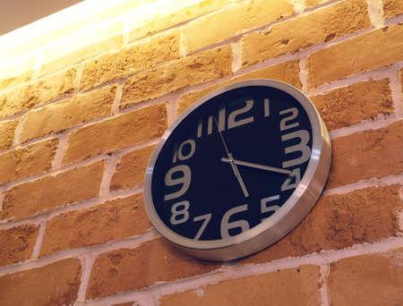 Black wall analog clock on brick wall in home interior