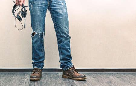 Jeune homme de mode en jeans et bottes avec un casque sur plancher en bois