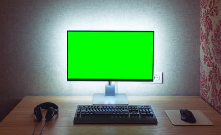 Blank chromakey monitor with keyboard and mouse with backlight over gray wall in dark room