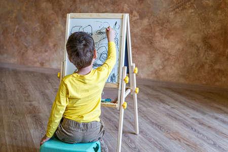Le jeune garçon s'assied et dessine sur la planche à dessin avec des feutres Banque d'images