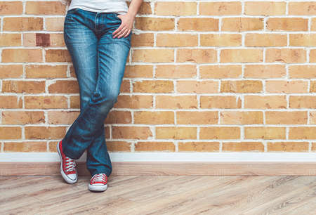 Woman legs in jeans and red sneakers, woman standing in front of brick wall, fashion concept Stock fotó