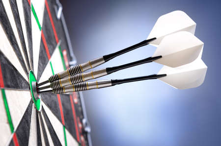 Three darts in bullseye of dartboard Stock Photo