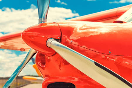 Detail of the propeller of a red airplane at the airport. Plane motor with propeller.