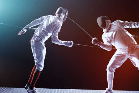 Fencing players isolated on black background. Isolated on black background.
