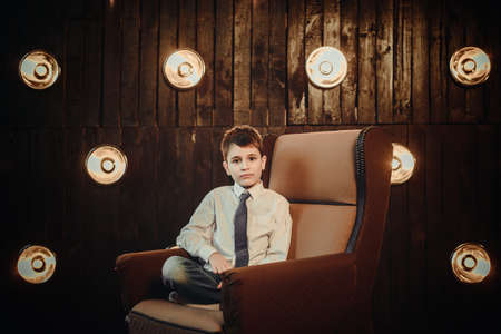 teenager boy: Young businessman in the armchair in front of lights wall