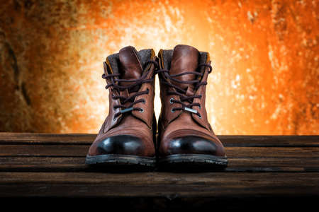 Footwear concept. Mens winter boots of brown colour isolated on rusty wooden background.