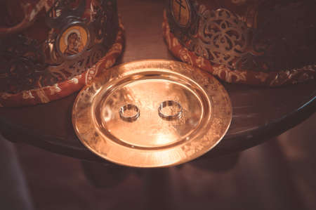 solemnization: two plain golden wedding rings on a copper salver, orthodox crowns
