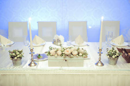 cater: Table set for a wedding dinner with flowers and candles Stock Photo