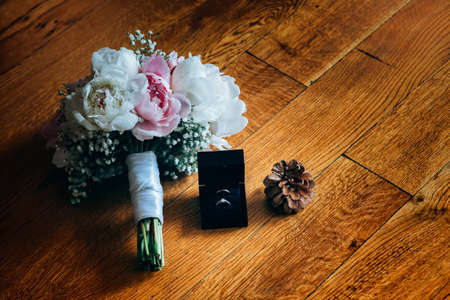 spica: Bridal bouquet of roses, wedding rings in the box and pine cone on a wooden planks Stock Photo