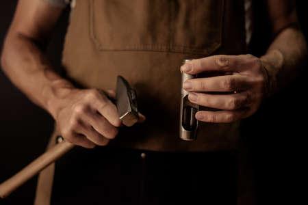 Mains tenant objet artisanal en cuir avec l'outil en utilisant pour la fabrication Banque d'images