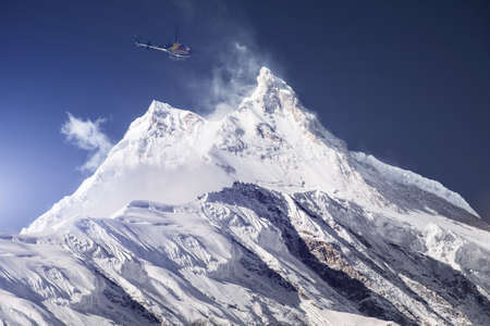 Rescue helicopter over snowy mountain peak