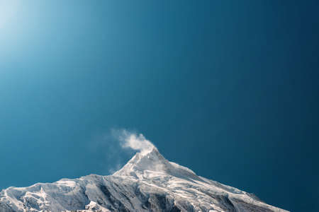 Le vent qui souffle la neige à partir du pic de montagne