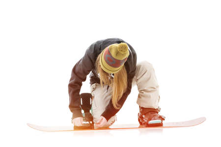 Young woman putting on snowboard Banque d'images