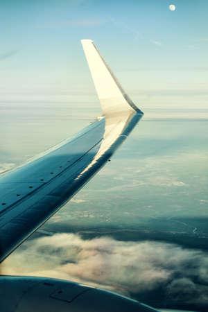 Aile d'un avion sur des nuages ??en face de la Lune