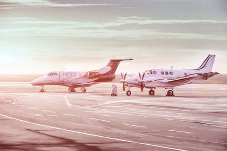 Private jet planes parking at the airport. Private airplanes at sunset, Banque d'images