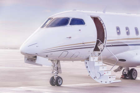 Private jet plane parking at the airport. Private airplane at sunset, 스톡 콘텐츠