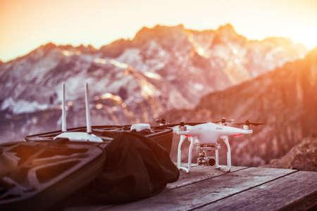Drone prêt à voler devant les hautes montagnes. Coucher de soleil au sommet des montagnes.