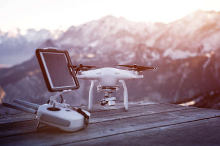 Drone ready to flight in front of high mountains. Sunset over top of mountains.