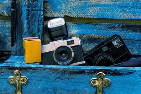 Ancienne caméra avec flash, boîtier de film et caméra noire sans miroir sur fond bleu en bois.