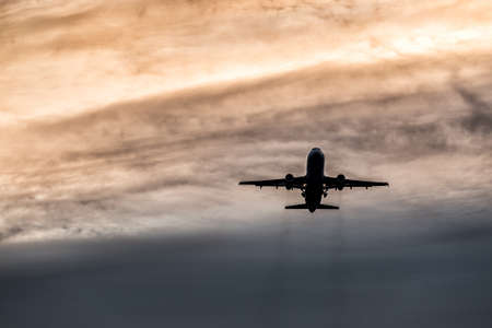 A commercial airplane during takeoff from the airport. Silhouette flying over sky at sunset or sunrise background,