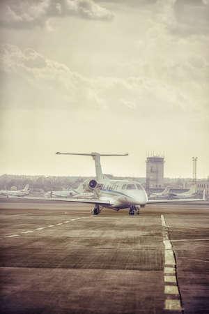 Stationnement à jet-jet privé à l'aéroport. Avion privé au coucher du soleil orange.