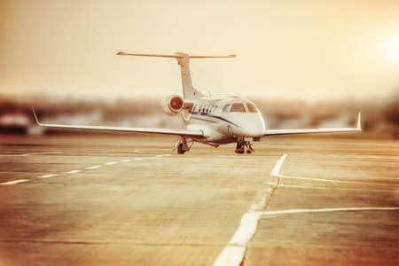 Private jet plane parking at the airport. Private airplane at orange sunset.